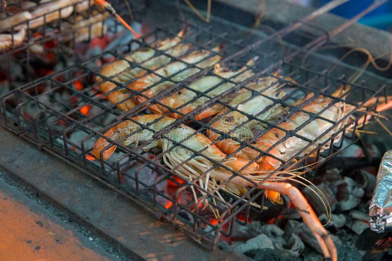 Roasted prawn grilled in rust steel grating on charcoal royalty free stock photo