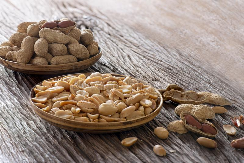 Roasted ha salato le arachidi e l'arachide ha sbucciato il piatto sulla tavola di legno fotografie stock libere da diritti