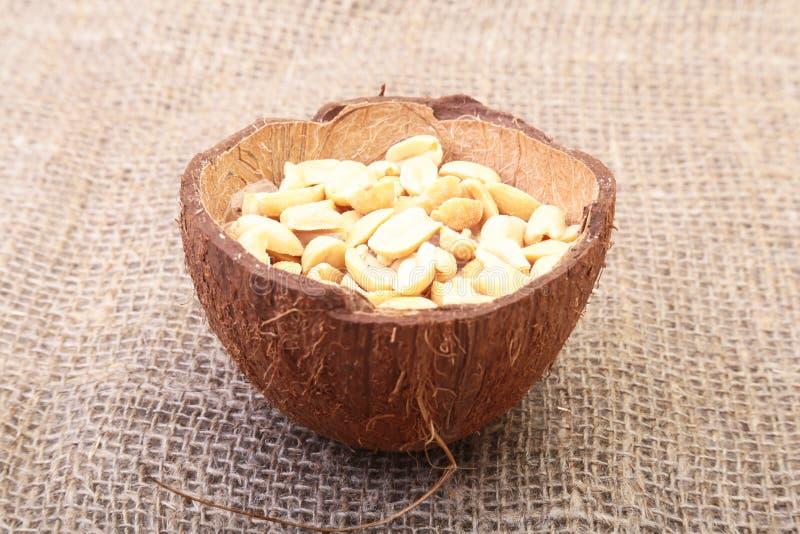 Roasted ha sbucciato le arachidi in ciotola fatta a mano di noce di cocco, fuoco selettivo fotografia stock libera da diritti