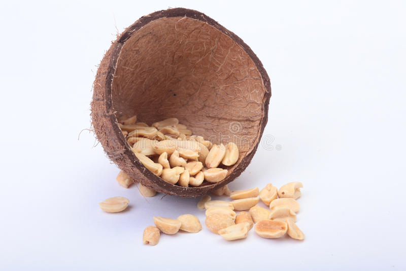 Roasted ha sbucciato le arachidi in ciotola fatta a mano di noce di cocco, fuoco selettivo immagine stock