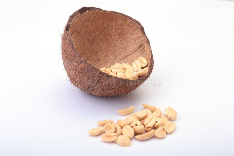 Roasted ha sbucciato le arachidi in ciotola fatta a mano di noce di cocco, fuoco selettivo immagini stock libere da diritti
