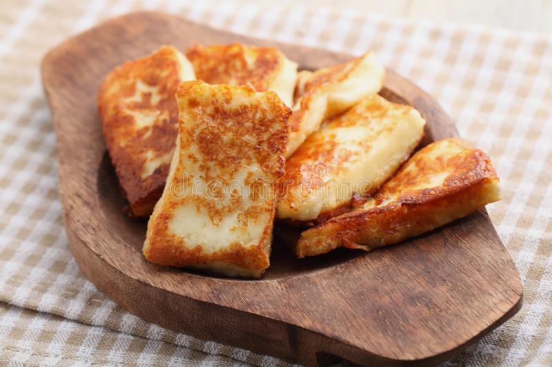 Roasted halloumi cheese in wooden tray stock photography