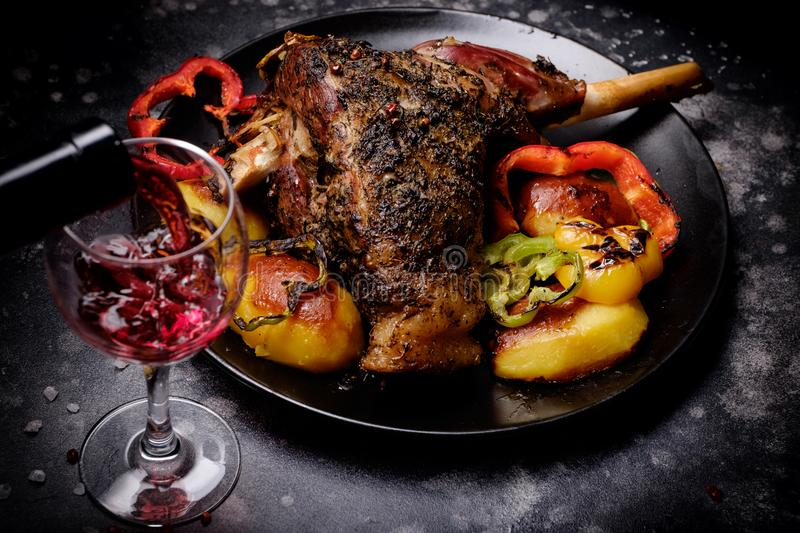 Roasted lamb shank with spices and grilled vegetables and red wine stock image