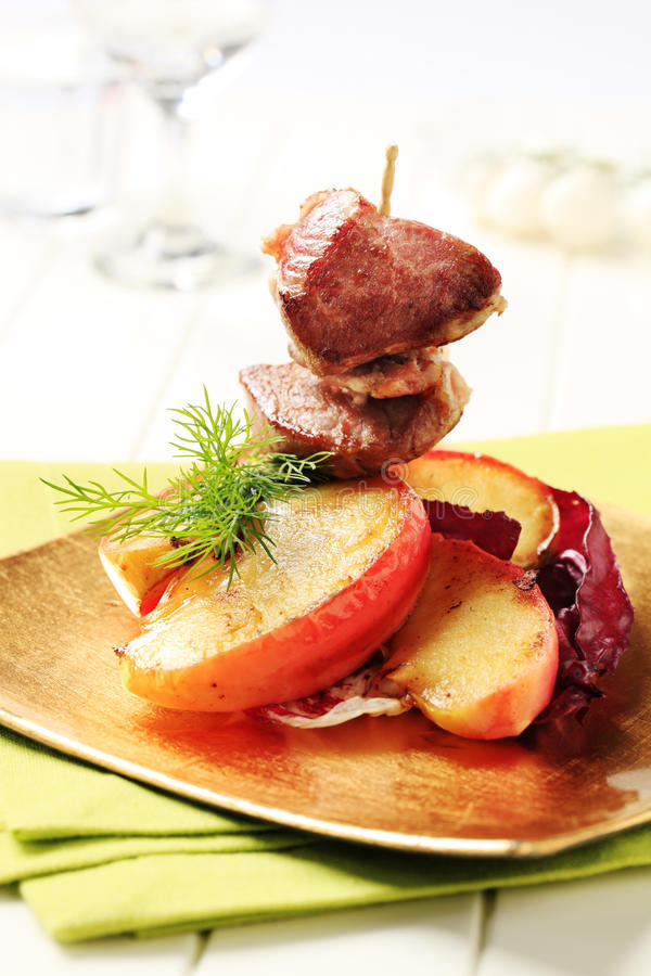 Roasted meat and baked apple stock image