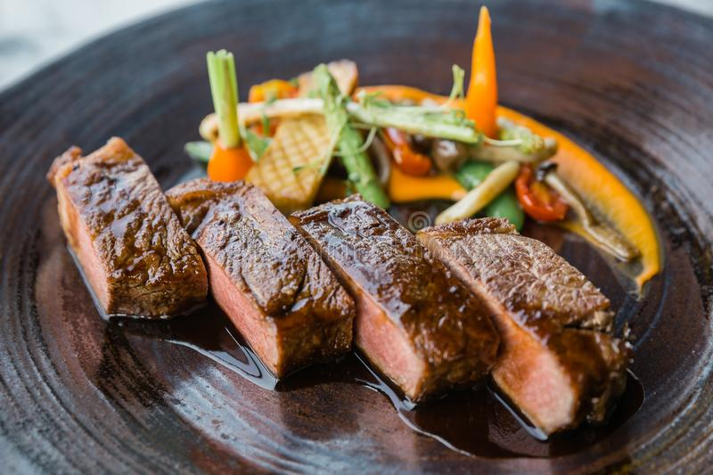 Roasted medium rare wagyu beef served with sour sauce with roasted baby vegetables on stone plate.  royalty free stock photography
