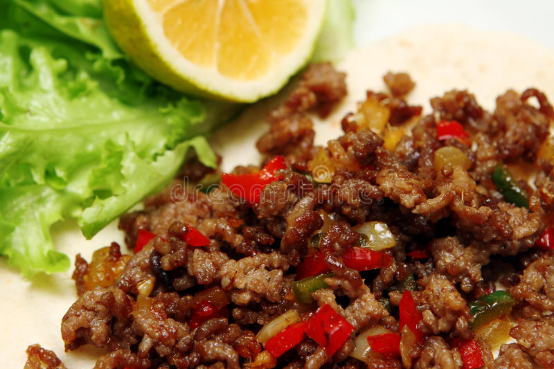 Roasted minced beef with chili pepper on tortilla with lettuce and lemon stock photos