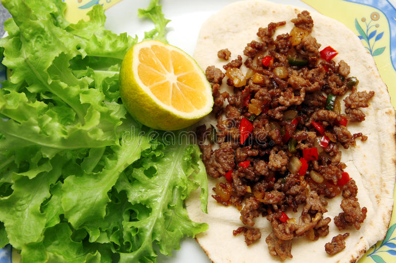 Roasted minced beef with chili pepper on tortilla with lettuce and lemon stock photography