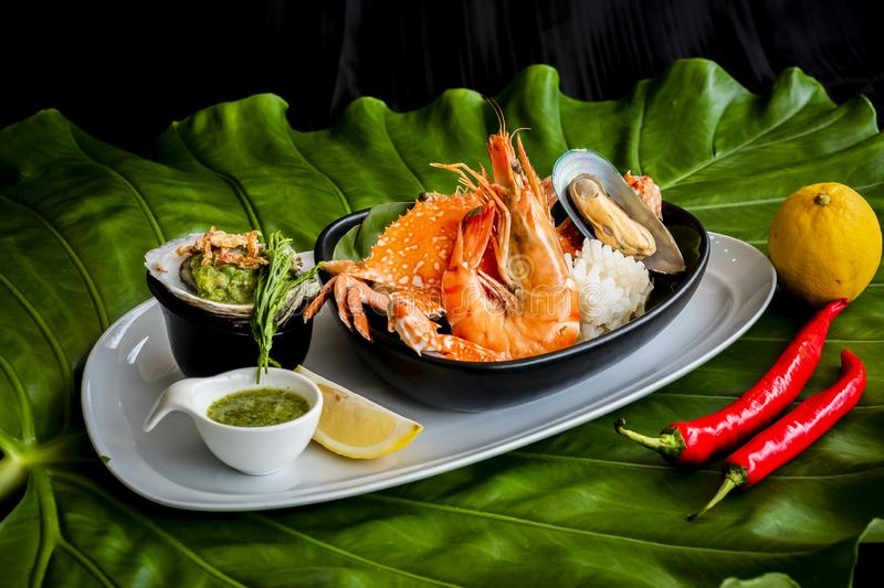 Roasted Mixed Seafood Contain Blue Crabs, Mussels, Big Shrimps, Calamari Squids with Spicy Chili Sauce and Lemon on Dish, on green stock photography