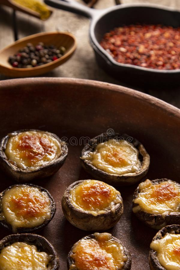 Roasted mushrooms with vegetables and parsley under melting cheese royalty free stock photo