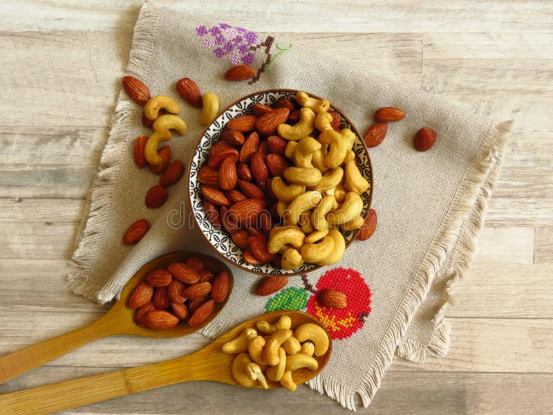 Roasted Natural Almond Nuts Badam and Cashew in a porcelain bowl. Two wooden spoons and Nuts spilled on handmade embroidered cloth royalty free stock image