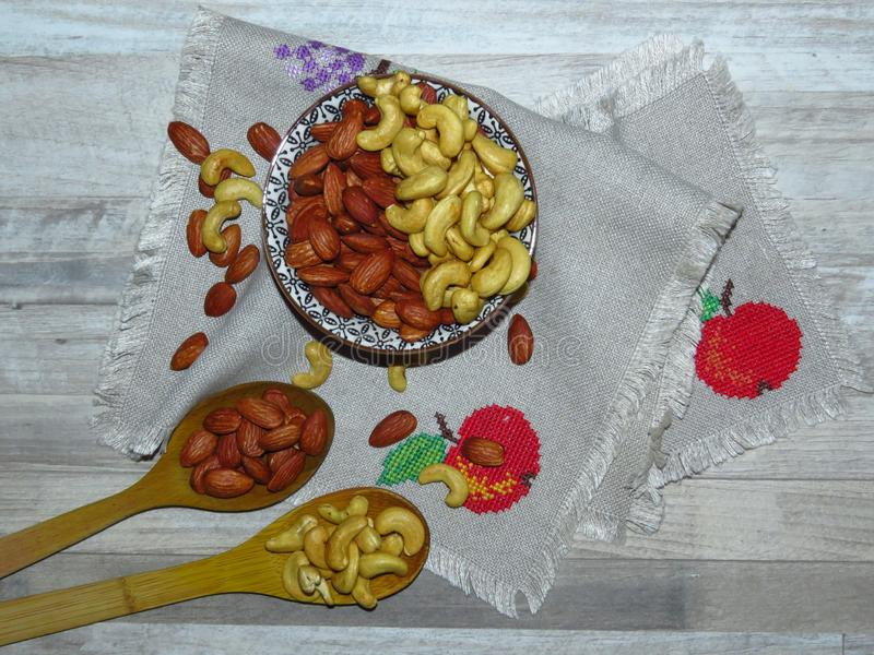 Roasted Natural Almond Nuts Badam and Cashew in a porcelain bowl. Two wooden spoons and Nuts spilled on handmade embroidered cloth. Roasted Natural Almond Nuts royalty free stock images
