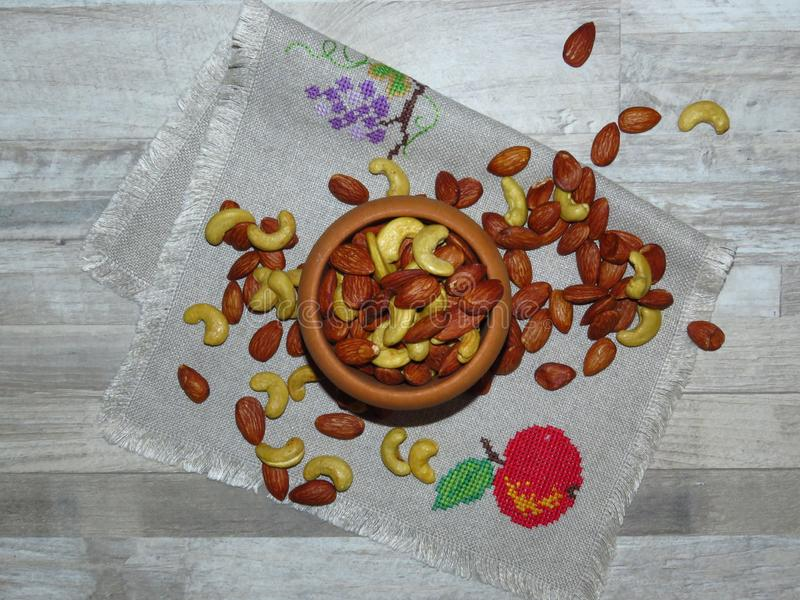 Roasted Natural Almond Nuts Badam and Cashew in an wooden bowl. Nuts spilled on handmade embroidered cloth. Bleached oak wood background. Space for text royalty free stock photo