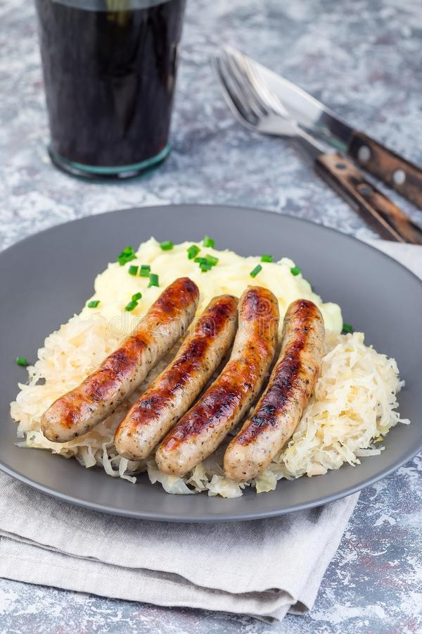 Roasted nuremberg sausages served with sour cabbage and mashed potatoes, vertical royalty free stock photos