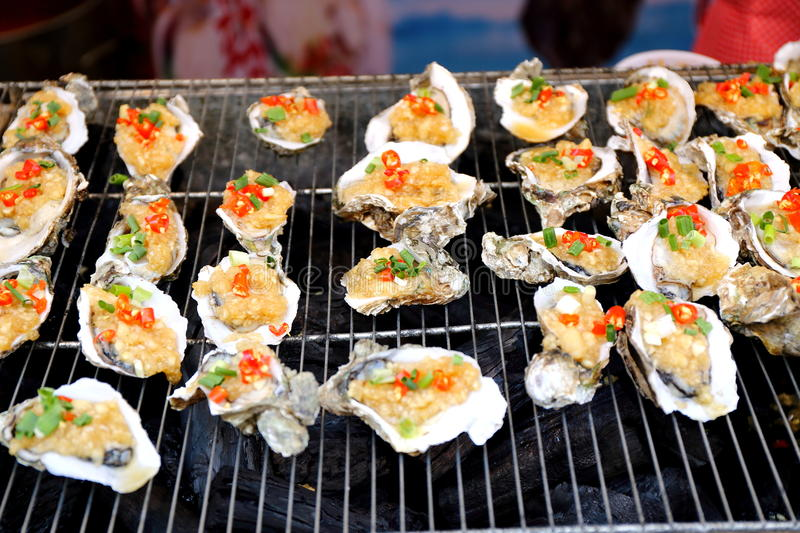 Grilled oyster seafood Chinese cuisine food. Roasted oysters with spices in restaurant in China Asia. Grilled fresh seafood. Exotic traditional Chinese cuisine stock photography
