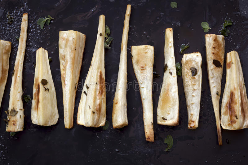 Roasted Parsnips on Black Overhead View stock images