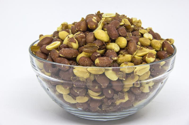 Roasted peanuts in glass bowl on white background royalty free stock photo
