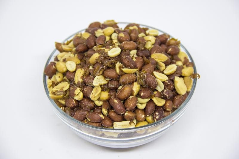 Roasted peanuts in glass bowl on white background stock photo