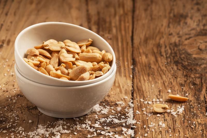 Roasted peanuts and salt in a bowl on a wooden background, selective focus stock image