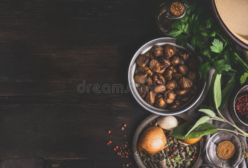 Roasted peló las castañas con los ingredientes para cocinar estacional sabroso en el fondo rústico oscuro, visión superior fotografía de archivo