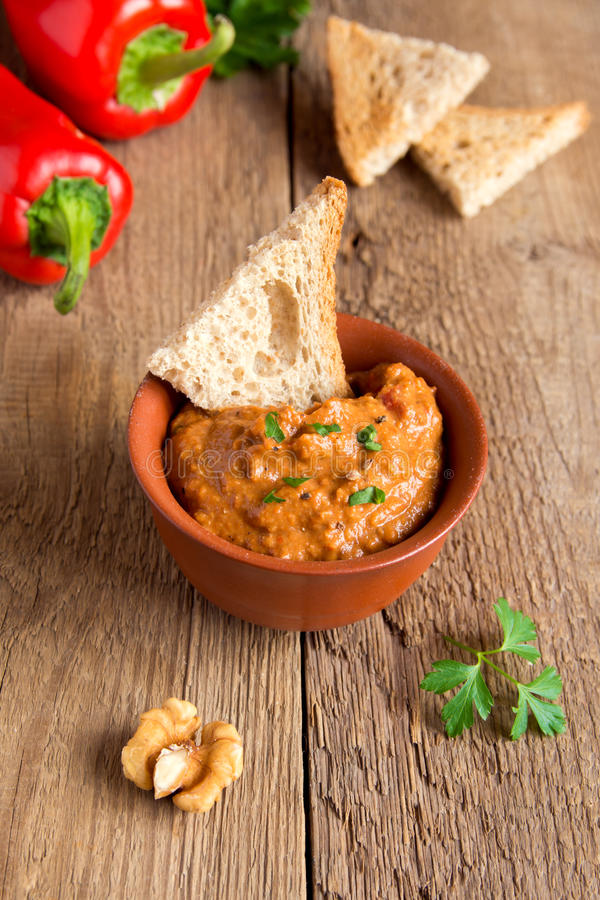 Roasted pepper dip. With nuts and bread in ceramic bowl over rustic wooden background closeup royalty free stock photos