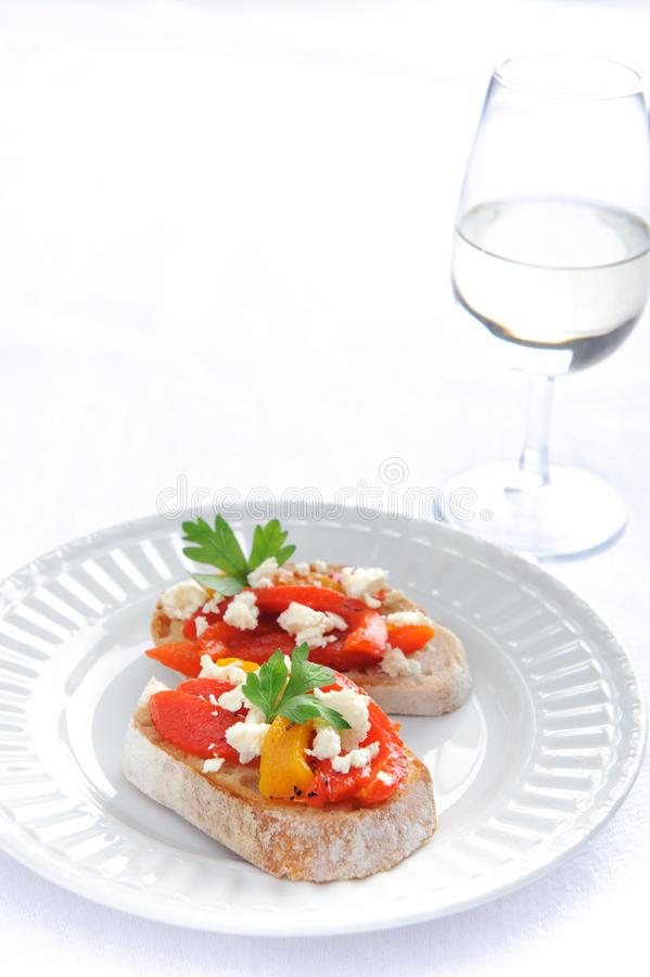 Roasted peppers canape. Slices of bagutte topped with roasted red and yellow peppers with feta cheese royalty free stock images