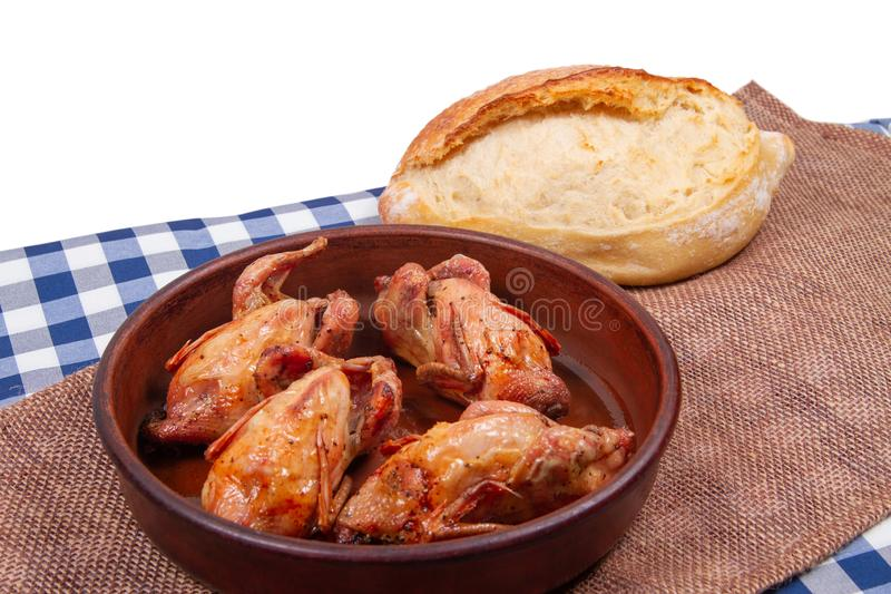 Roasted pigeon in clay pot and loaf of white bread lie on rustic table stock images