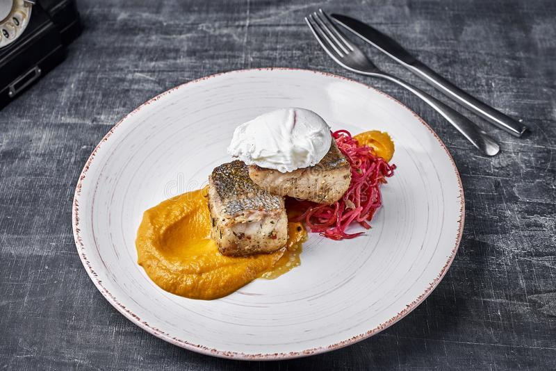 Roasted Pike perch with vegetable noodles and egg. Close up, selective focus. Dietary menu. Fish menu. Seafood. Concept royalty free stock photography
