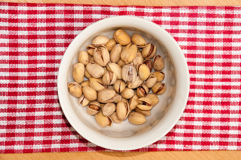 Roasted pistachios in a bowl on red tablecloth royalty free stock photo
