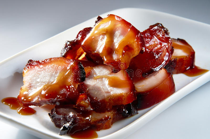 Roasted Pork. Still life on roasted pork cut in slide and serve on white plated stock image