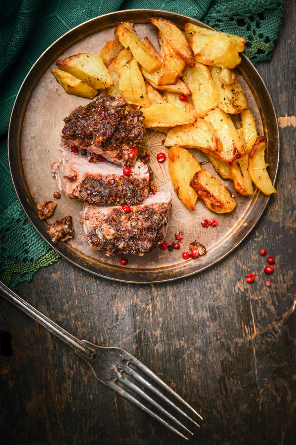 Roasted Pork fillet with a crust and baked potato in plate with fork ,top view royalty free stock photo