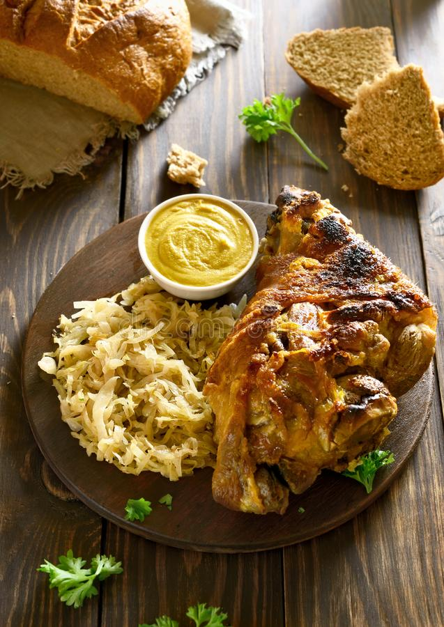 Roasted pork knuckle. Eisbein with braised cabbage sauerkraut and mustard on wooden table royalty free stock images