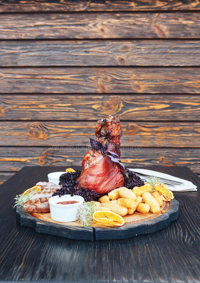 Roasted pork or lamb leg with sauce. Fried pork leg with sauce on a cutting wooden board. wooden background royalty free stock image