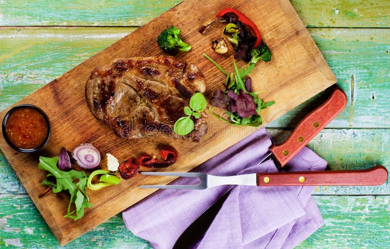 Roasted Pork Neck. Delicious Roasted Pork Neck with Grilled Vegetables, Fresh Greens and Hot Sauce closeup on Wooden Cutting Board with Meat Fork and Knife. Top stock photography