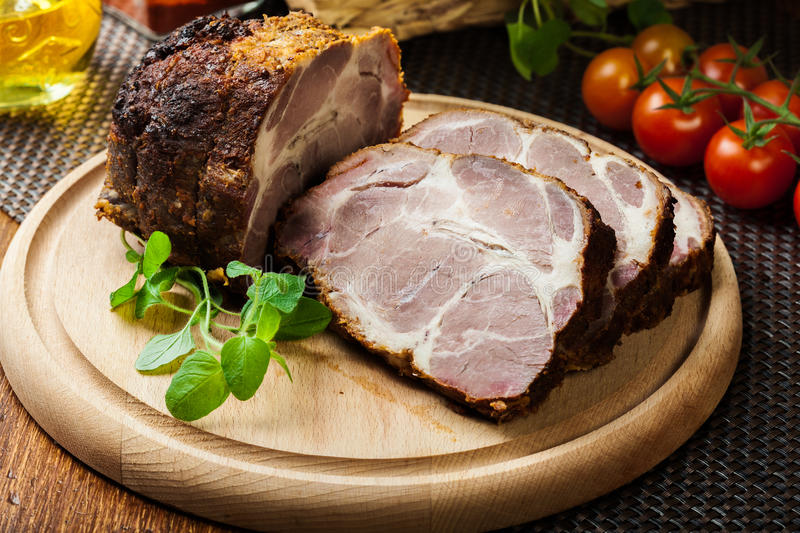 Roasted pork neck with spices. On cutting board stock image