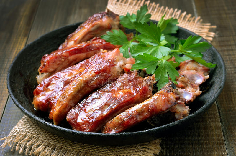 Roasted pork ribs in frying pan. Close up stock photography