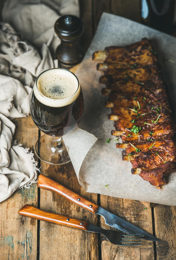Roasted pork ribs with garlic, rosemary and glass of beer royalty free stock photography