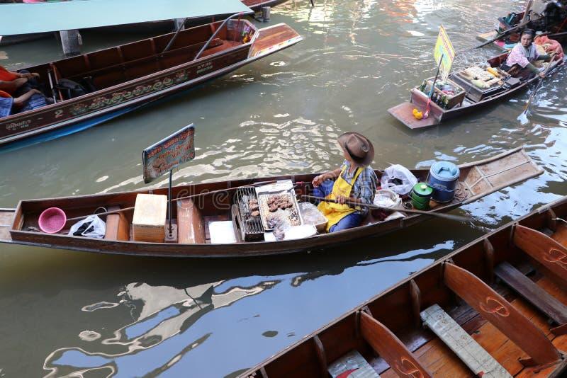 Roasted pork seller sitting on his boat in the canal at Damnoen Saduak floating market stock image