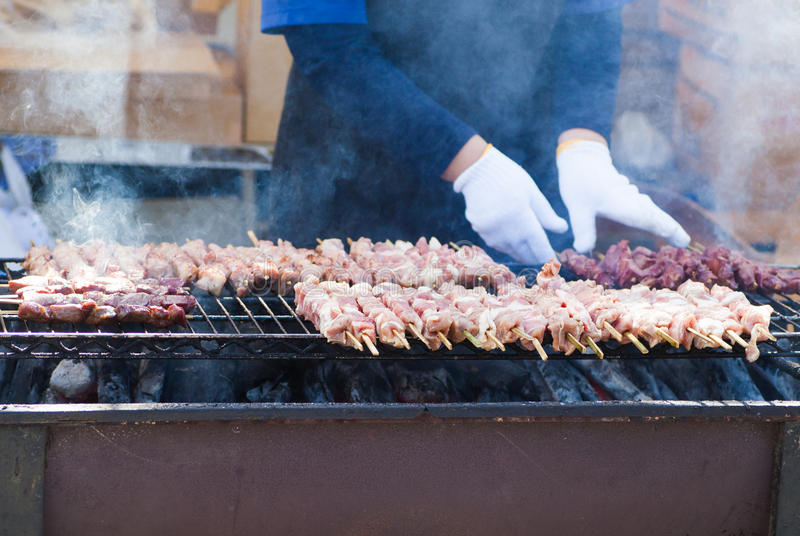 Roasted pork with skewer. On Flaming BBQ Grill royalty free stock photo
