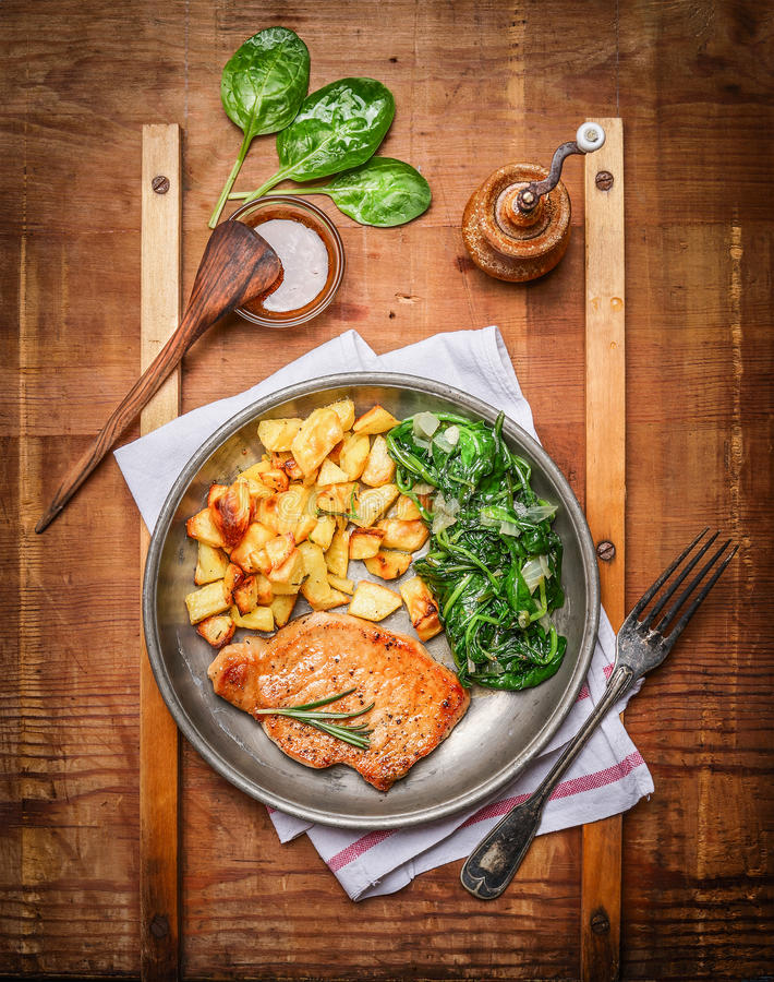 Roasted pork steak, baked potatoes and cooked spinach in rustic metal plate on wooden background royalty free stock images