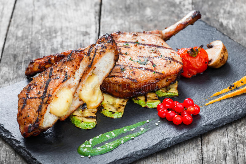 Roasted Pork steak on bone stuffed with cheese, grilled vegetables and berries on stone slate background on wooden background royalty free stock photo