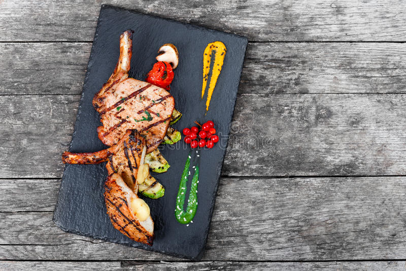 Roasted Pork steak on bone stuffed with cheese, grilled vegetables and berries on stone slate background on wooden background. Close up. Hot Meat Dishes. Top stock photos