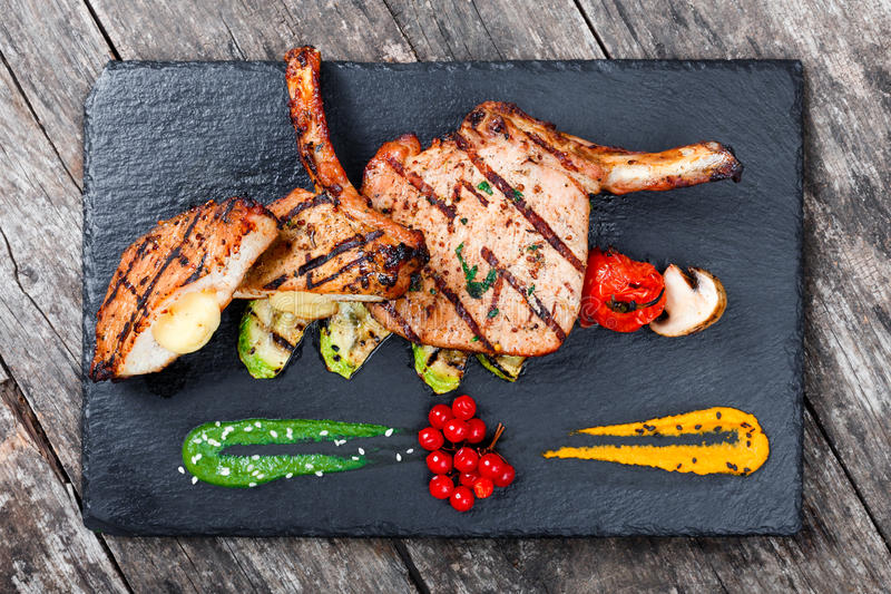 Roasted Pork steak on bone stuffed with cheese, grilled vegetables and berries on stone slate background on wooden background stock photo