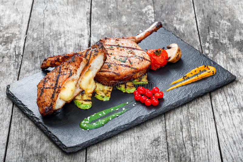 Roasted Pork steak on bone stuffed with cheese, grilled vegetables and berries on stone slate background stock images