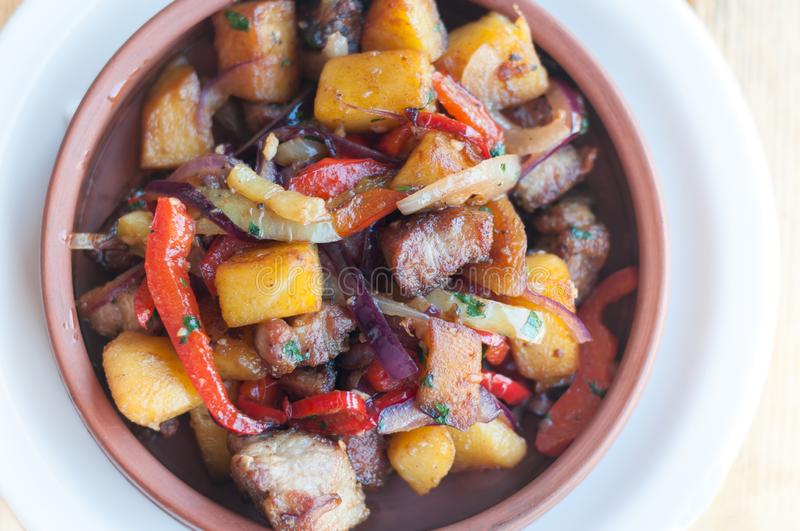 Roasted pork with steamed vegetables: potato, onion, bell pepper in the ceramic plate. Caucasian georgian food ojahuri. royalty free stock images