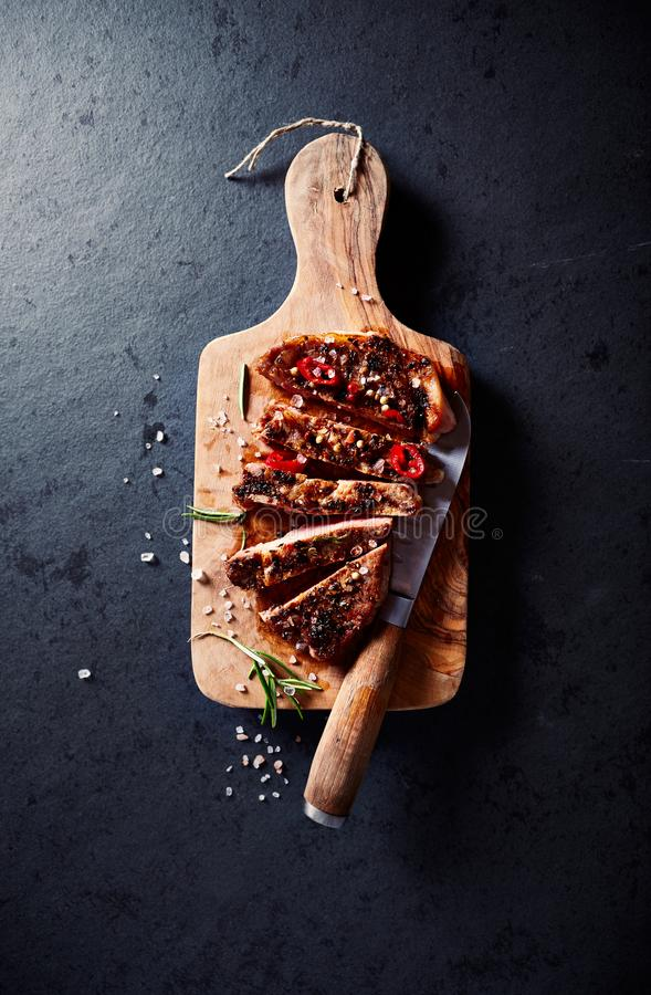 Roasted pork tenderloin on a chopping board. Top view. Copy space. Black, stone background royalty free stock photo