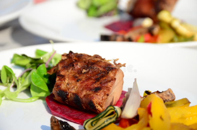 Roasted pork tenderloin with vegetables on a plate stock photos