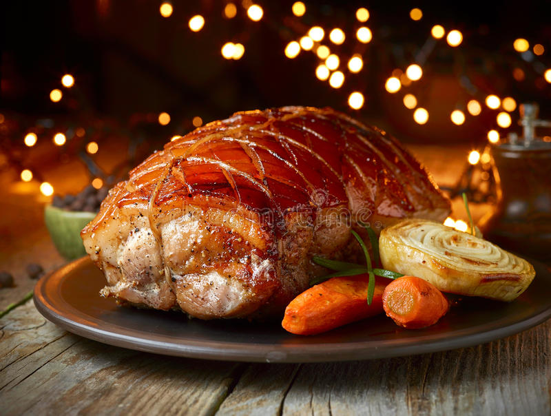Roasted pork and vegetables. On Christmas lights background royalty free stock images