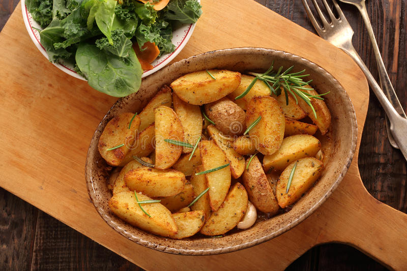 Roasted potato in brown bowl with fresh salad on wooden table. Roasted potato in brown bowl with fresh kale salad on wooden table royalty free stock photo