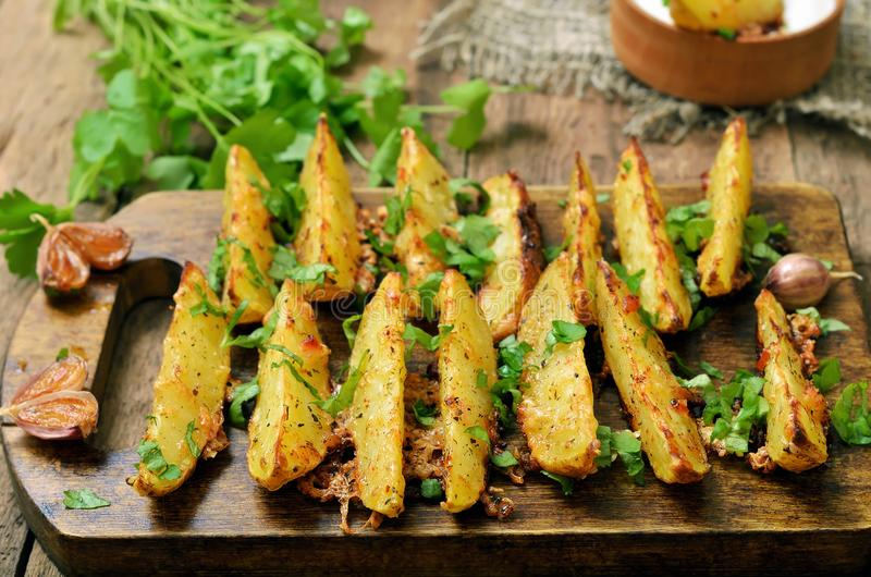 Roasted potato wedges. With parsley on cutting board stock photos