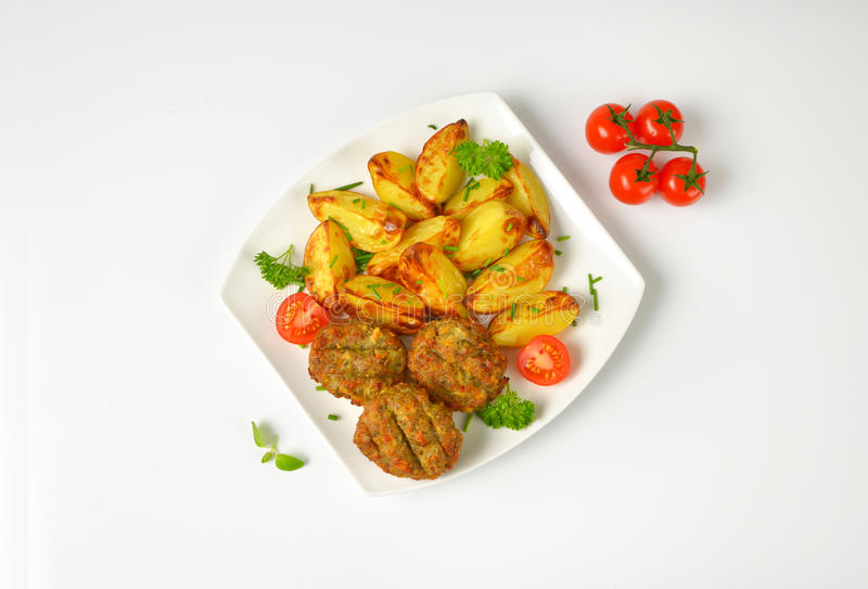 Roasted potatoes and fried meatballs. Plate of roasted potatoes and fried meatballs on white background stock image